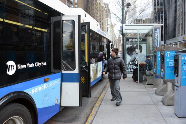 Går i New York men ännu inte i Stockholm. New Yorks Select Bus Services har påstigning även genom bakdörrarna. Biljett köper man i automat på hållplatsen – på den här bilden syns tre biljettautomater till höger. Foto: Ulo Maasing.