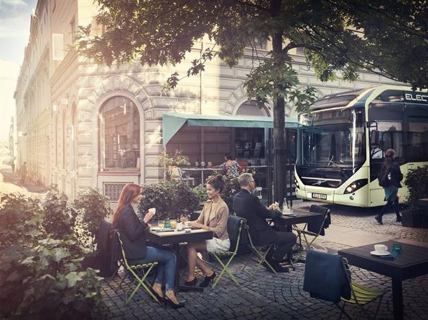 För att lyfta fram hur tyst bussen är använder sig Volvo av en bild som visar den nya elhybridbussen smyga fram förbi en uterestaurang utan att störa samtalen vid borden. Bild: Volvo Bussar.