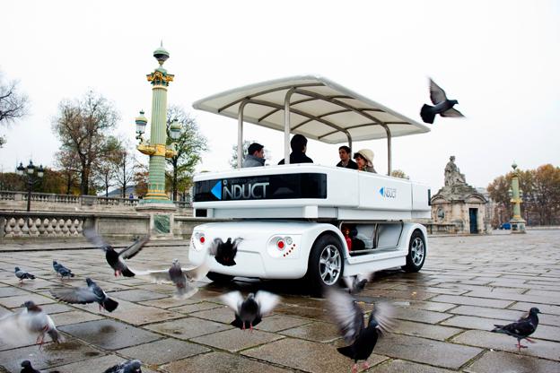 En förarlös liten buss trafikerar tekniska högskolans område i Lausanne. Foto: Induct.