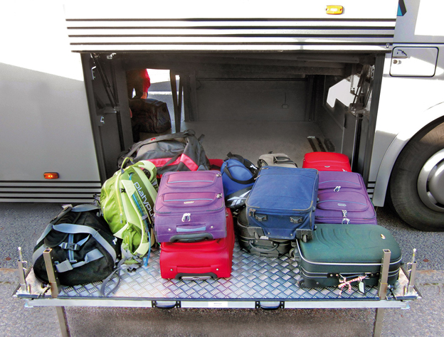 Slut med lyft för bussförare: Resenärerna ställer själva sitt bagage på vagnen som sedan skjuts in i bussens bagageutrymme.
