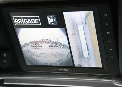 Ett avancerat kamerasystem gör att föraren kan se allt som sker och alla hinder runt bussen i en monitor ovanför vindrutan. På den här bilden visar monitorns vänstra del allt som finns bakom bussen, medan den högra delen visar bussen uppifrån. Man ser tydligt en person som står vid bussens främre högra hörn, likaså att bakdörren är öppen på bussen som står vid trottoarkanten. Foto: Ulo Maasing.