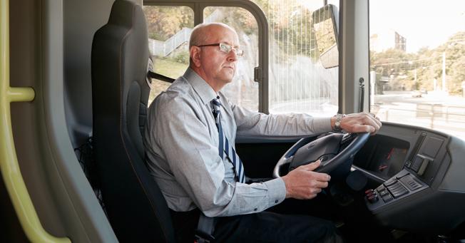 En förare bakom ratten på en elbuss. Den typiske bussföraren i Sverige är man som har kommit en bit upp i åren.Foto: Volvo.