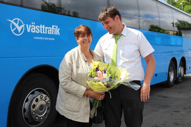 Niclas Höglund, gruppchef på Nobina Skaraborg, delar ut blommor till kunden Ann-Britt Lundqvist från Töreboda, och tackar henne för att hon åkt tagit bussen i 37 år. Foto: Nobina.